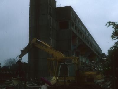View of 7-storey blocks undergoing demolition with 24-storey block to right of image